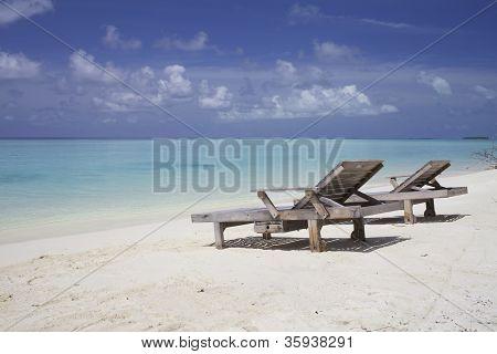 Lounge chairs on white sand beach