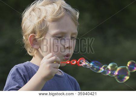Side View Of A Boy With Soap Bubbles.