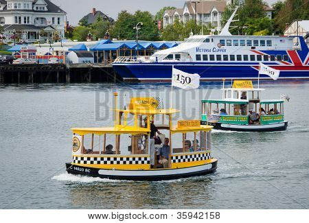 Two colorful water taxis ferry people around the waterfront of Victoria, British Columbia