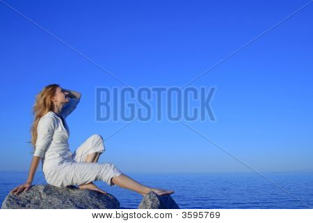 Relaxed Young Woman Enjoying Sunset By The Sea