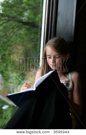 Natural Light Portrait Of Young Girl Writing In Her Journal On The Window Seat