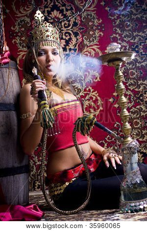 Beautiful Swarty Young Princess With Original Jewels And In A Gold Helmet Smokes A Hookah And Lets O