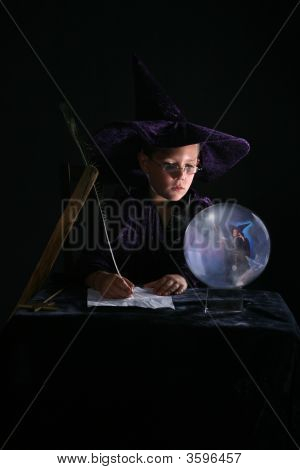 Child Wizard Writing A Spell And Gazing Into Crystal Ball