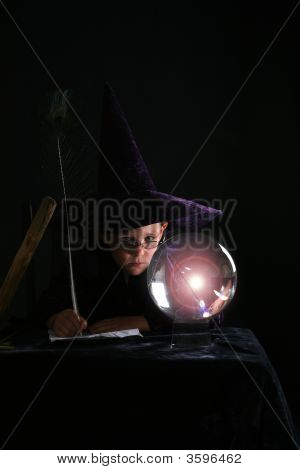 Child In Wizard Costume Gazing Into Crytal Ball