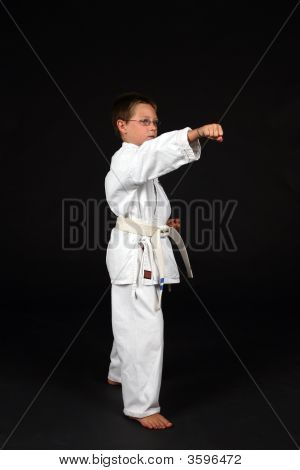 Side View Of Young Boy Demonstrating Right Stance With A Punch
