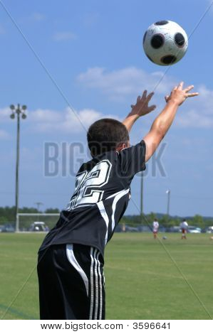 Boy Throwing A Soccer Ball Back In The Game.
