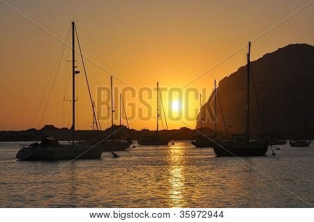 Sunset over bay and sailboats