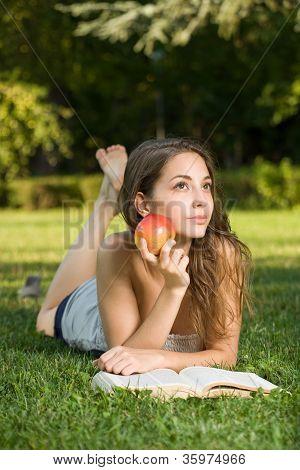 Linda joven morena en la lectura del parque.