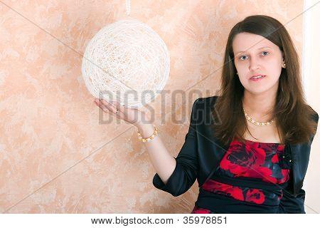 Girl Sitting Near A White Sphere