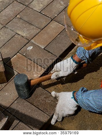Road Worker In Yellow Helmet Lays Tile Pavement