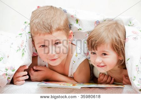 brother and sister reading a book on the bed