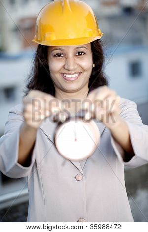 Female Construction Engineer Holding Alarm Clock