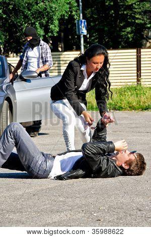 Hombre ladrón robar un coche, mientras que su cómplice distrae Driver femenino