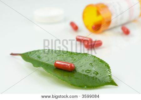 Red Pill Over A Green Leaf With Some Water Drops On It