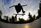 stock photo of skateboarding  - perfect silhouette of a skateboarder at a stylisch trick - JPG