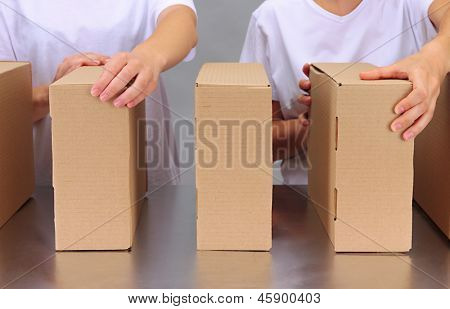 Workers working with boxes at conveyor belt, on grey background