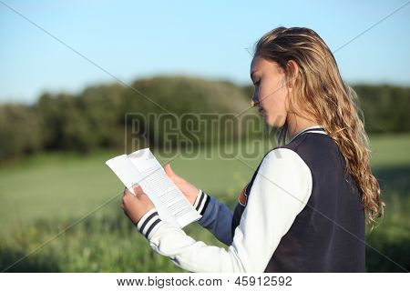 Back View Of A Beautiful Teen Girl Reading A Book