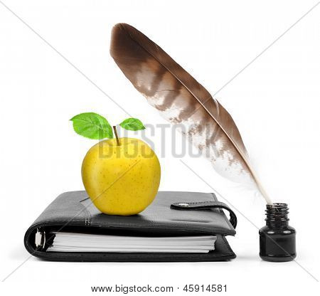 Feather in ink bottle and workbook with an apple