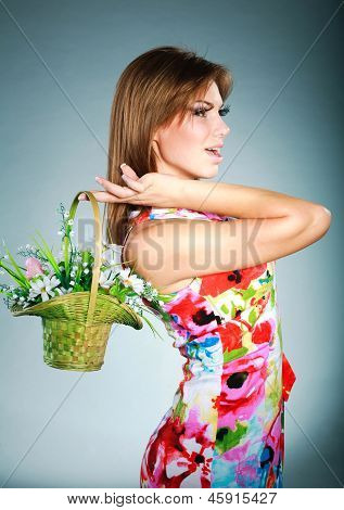 Attractive Brunet Girl In Colorful Dress With Flowers Basket,studio Shot,gray Background