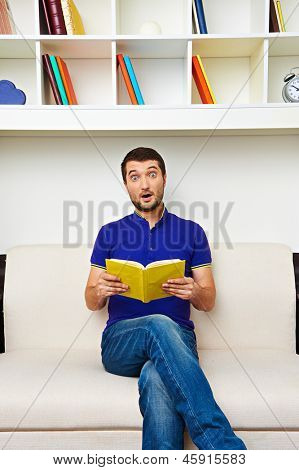young man holding book and looking at camera with astonishment