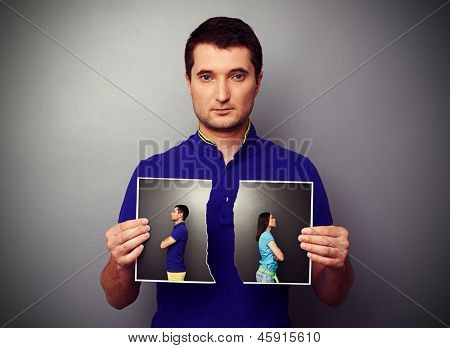 serious young man holding the lacerated photo of young couple in quarrel