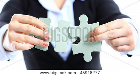 Business woman showing two jigsaw puzzle pieces