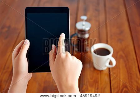 Young woman uses tablet while relaxing at home with coffee on the sofa couch
