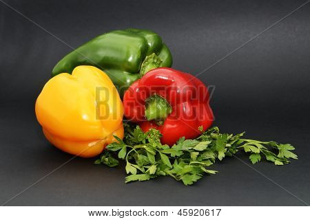 Sweet peppers with parsley isolated on a black background