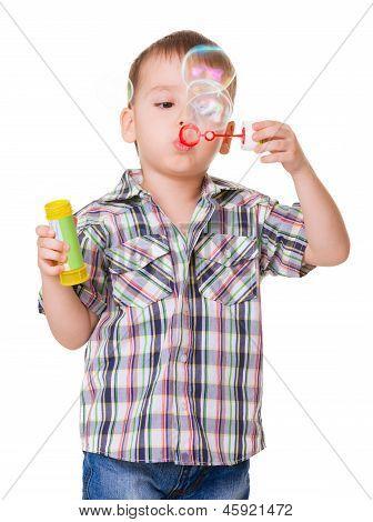 Boy Blowing Soap Bubbles On White