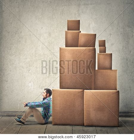 young man sitting on the floor with many boxes