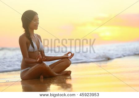 Relaxing and meditation - Yoga woman meditating at serene beach sunset. Girl relaxing in lotus pose in calm zen moment in the ocean water during yoga holidays resort retreat. Multiracial girl.
