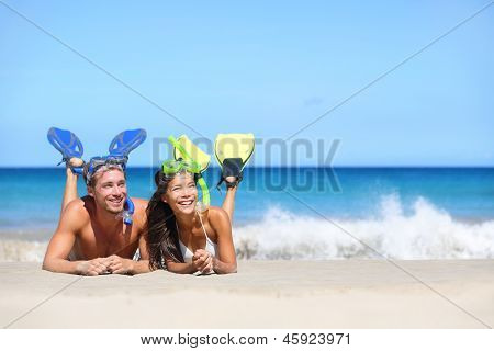 Beach travel couple having fun snorkeling. Happy young multiracial couple lying on summer beach sand with snorkel equipment looking to side at copy space after swimming with fins and mask on vacation.
