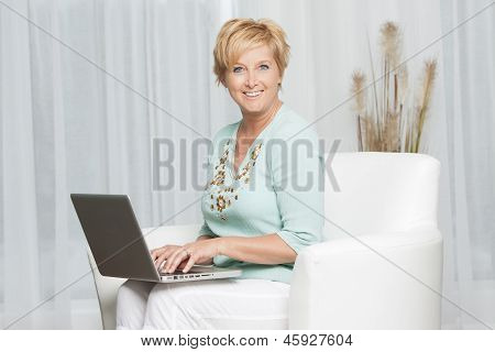 Portrait of a happy woman sitting using laptop