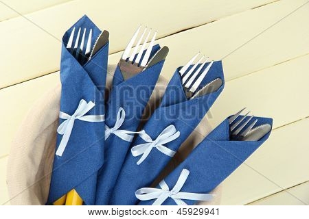 Forks and knives wrapped in blue paper napkins, on color wooden background