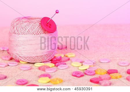 Beautiful buttons and a ball of yarn on a pink background