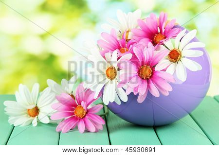 Pot with flowers on a wooden table on the nature background