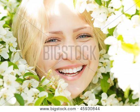 Closeup laughing woman among blossom tree