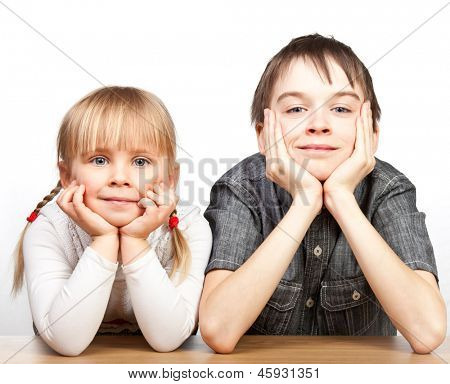 Portrait of cute girl and boy sitting at desk with hands on chin