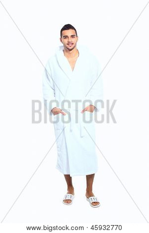 Adult man in bathrobe standing on white background