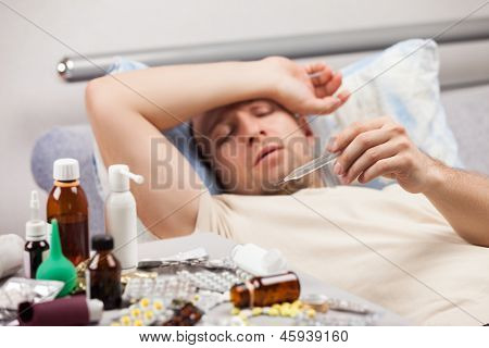 Adult man patient holding high temperature thermometer lying down bed for cold and flu illness relief