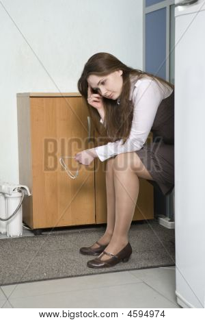Upset Clerk Sitting In The Corner Of Corridor Of Office