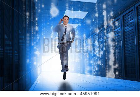 Businessman running through data center with glowing computer matrix