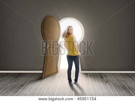 Woman walking towards keyhole shaped doorway with light dark grey room
