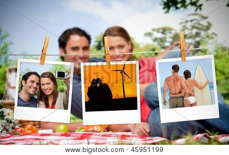 Serial instant photos of holiday scenes hung with a peg on a laundry line with couple having a picnic on the background