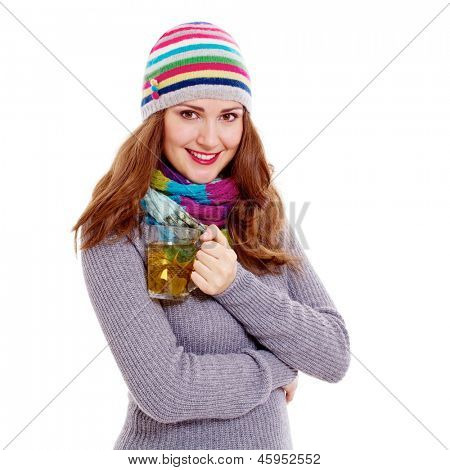 Young woman in warm dress, colorful scarf and cap with hot cup of green tea. Isolated on white background, mask included
