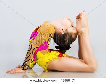 little girl gymnast on a light background
