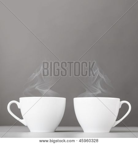 cups of hot coffee on gray background