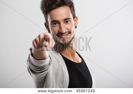 Handsome young man looking and pointing to the camera, over a gray background