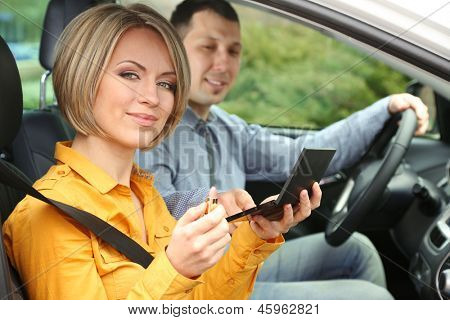 Portrait of young beautiful couple sitting in the car (woman applying makeup)