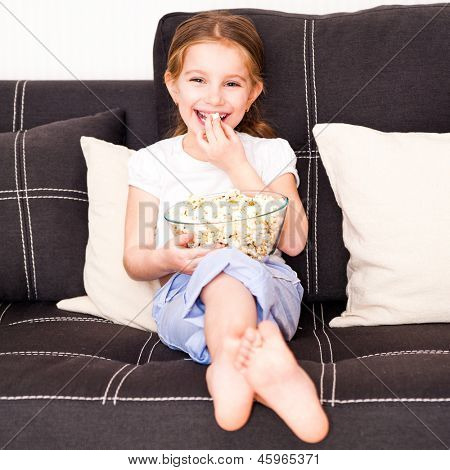 girl eating popcorn in front of TV